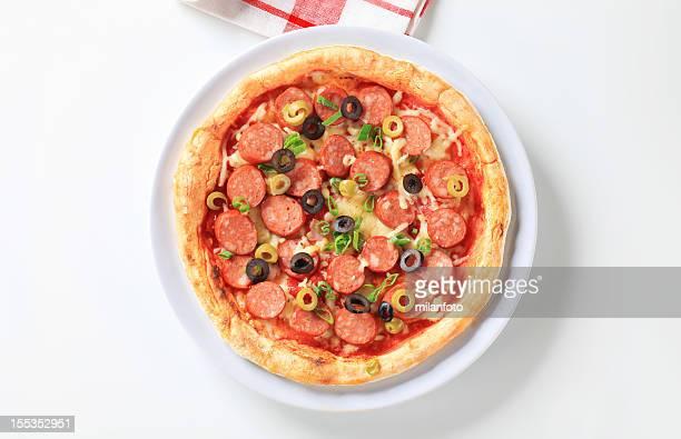 Pizza und salami auf einer Platte