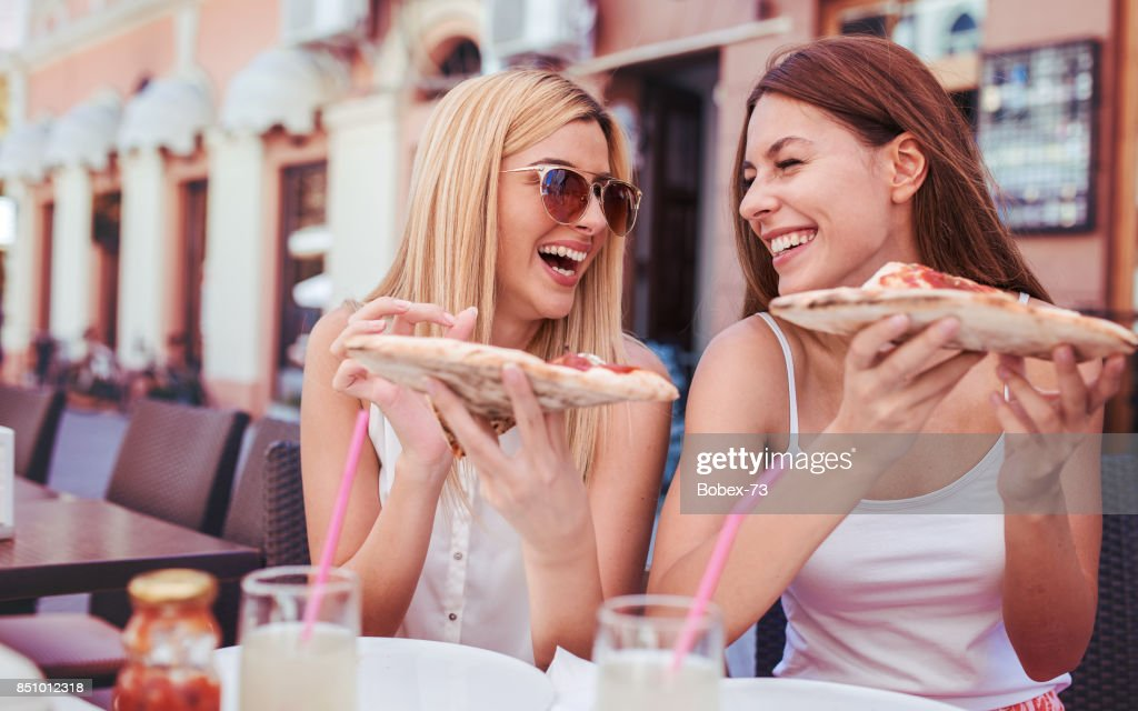 Pizza time. Young girls eating pizza in a cafe. Consumerism, lifestyle : Stock Photo