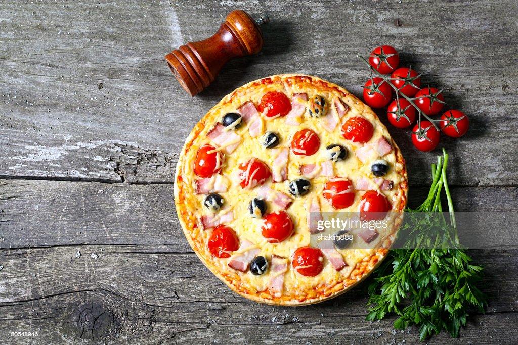 pizza con tocino, aceitunas, tomate : Foto de stock