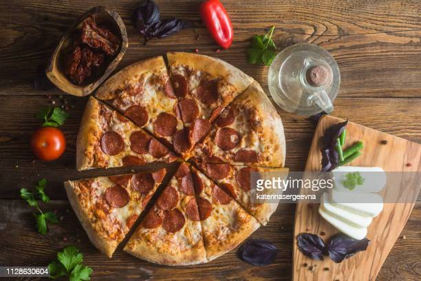 pizza with cheese, pepperoni, chicken and pepper, a slice for a gourmet dinner - pepperoni pizza stock photos and pictures