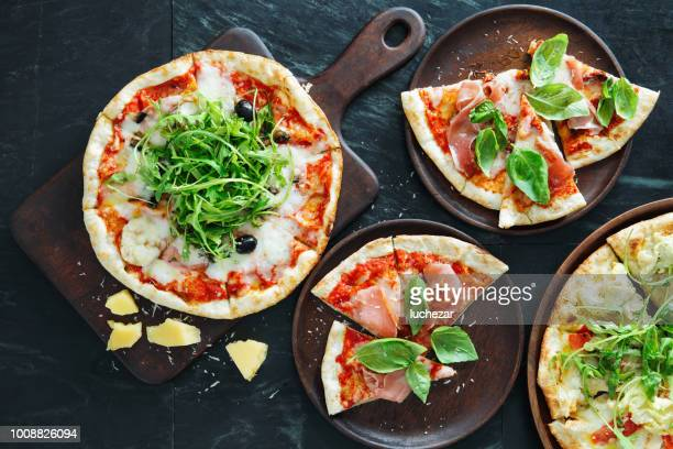 pizza with ham, olive and arugula - stone object stock pictures, royalty-free photos & images