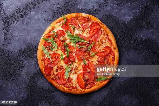 Pizza with ham, tomato and arugula leaves on dark background