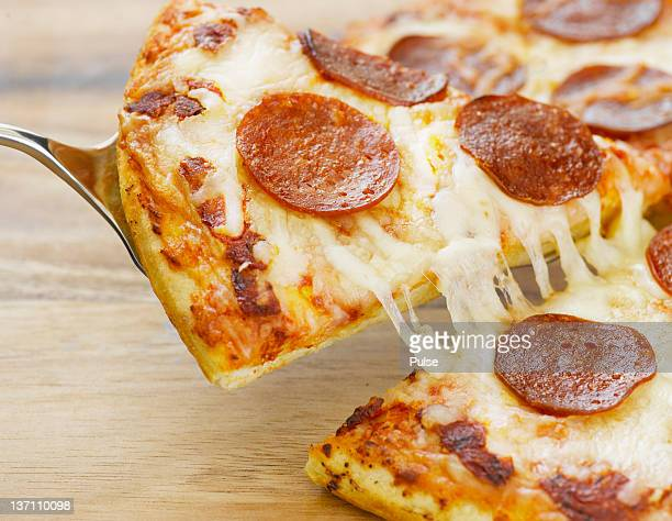 Pizza with salami being sliced