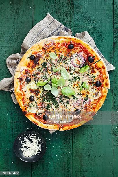 Pizza with tomato sauce, mozzarella, mushrooms, herbs and artichokes
