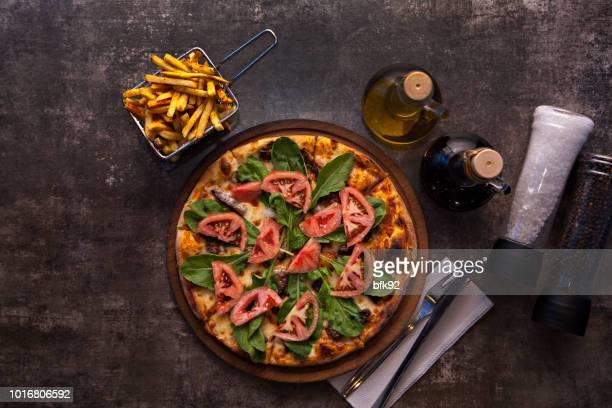pizza com tomate, queijo mussarela e rúcula. - table top - fotografias e filmes do acervo
