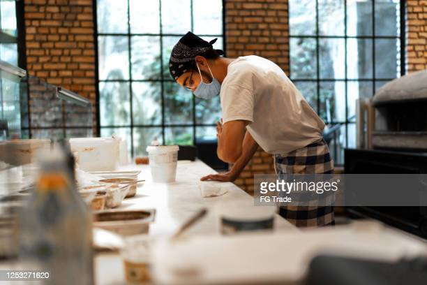 pizzaiolo with face mask preparing pizza at restaurant - pizzeria stock pictures, royalty-free photos & images