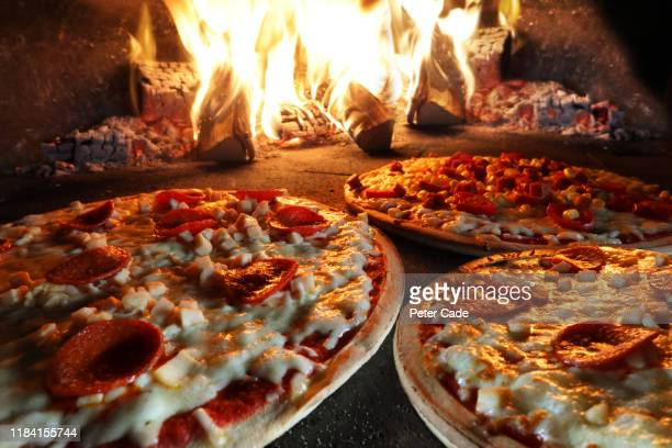 pizzas in pizza oven - pizza stock pictures, royalty-free photos & images