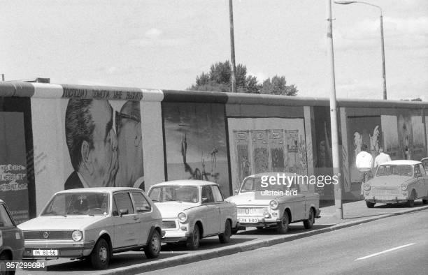 Pkw der Marke Trabant stehen an der Mühlenstrasse in Ostberlin vor den Bildern Bruderkuss gemalt vom russischen Maler Dmitri Waldimirowitsch Wrubel...