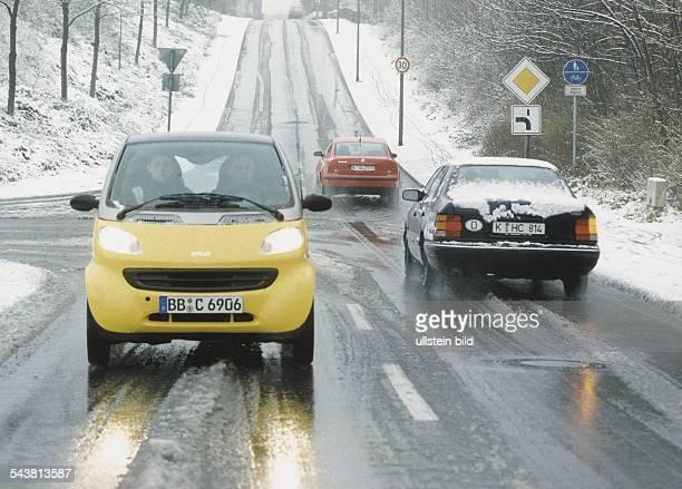 PKWs fahren auf einer verschneiten Landstraße. Auf der Fahrbahn befindet sich schimmernder Schneematsch, am Straßenrand liegt weißer Schnee. Ein...