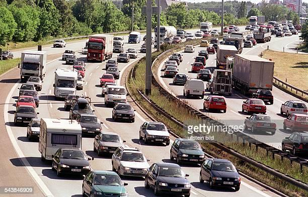 PKWs und LKWs stehen im Stau auf der Autobahn bei Hamburg. Auch Campingwagen und Wohnmobile befinden sich in dem zähfließenden Verkehr. Autobahn,...