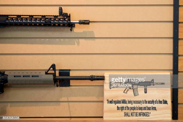 A placard about gun rights in the United States hangs on the wall next to assault rifles for sale at Blue Ridge Arsenal in Chantilly Virginia on...