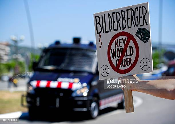 A placard against the Bilderberg Group meeting is held in front of a antiriot van on June 3 2010 in Sitges near Barcelona Police blocked the...