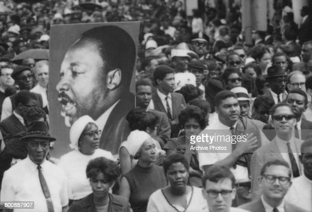 A placard bearing a portrait of Martin Luther King Jr in the 150000strong crowd following the coffin of the assassinated American civil rights leader...
