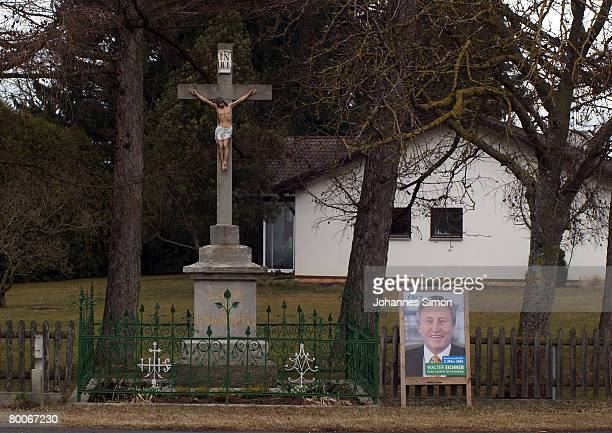 Placard campaigning for local politician Walter Eichner is seen beside a wayside commemorative cross on February 29, 2008 in Untermuehlhausen,...