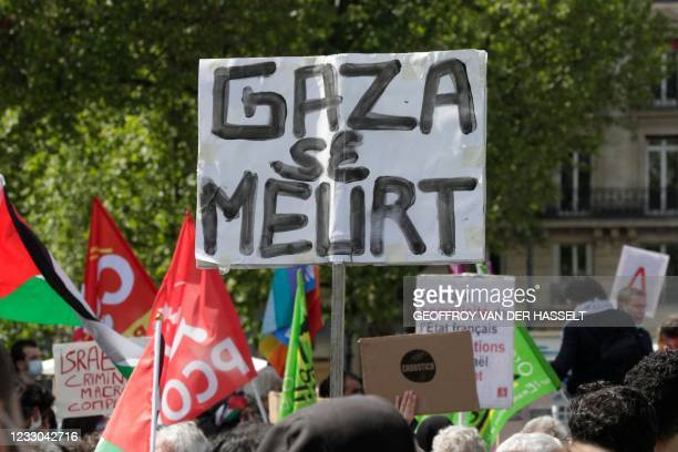 """Placard is displayed reading """"Gaza is dying"""" as protesters shout slogans and wave Palestinian flags during a demonstration in solidarity with the..."""