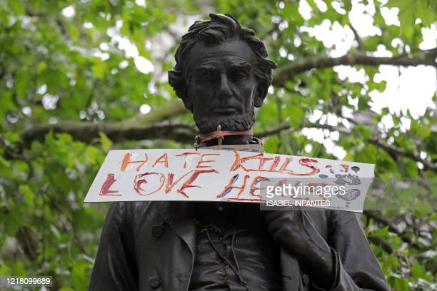 A placard is seen attached to the statue of former US President Abraham Lincoln in central London on June 7 left over from a Black Lives Matter...