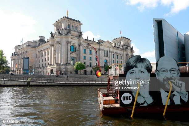 A placard on a boat featuring German Chancellor Angela Merkel and her challenger Martin Schulz leader of Germany's social democratic party drinking...