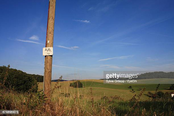 Placard On Wooden Post At Field Against Sky