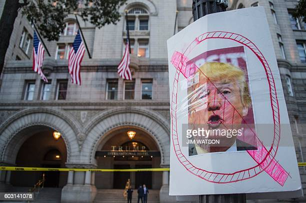 TOPSHOT A placard placed by protesters from Answer Coalition stands outside the Trump International Hotel in Washington DC September 12 ahead of the...