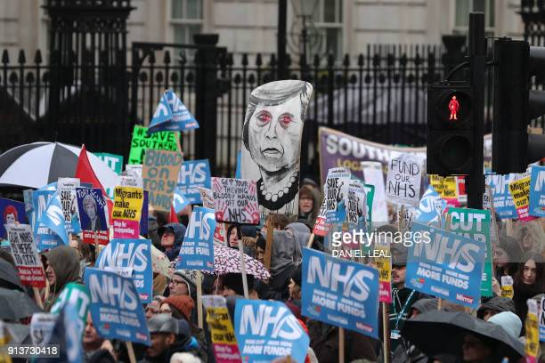 TOPSHOT A placard portraying Britain's Prime Minister Theresa May is held by protesters during a march calling for an end to the 'crisis' in the...