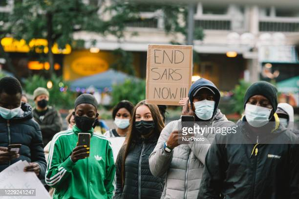 """Placard """" End SARS now"""" is seen during the protest over nigerian police brutality in Cologne, Germany, on October 23, 2020."""