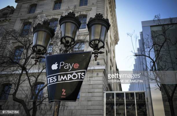 A placard reading Apple pay your taxes is seen attached to a street light during a gathering of activists of the Association for the Taxation of...