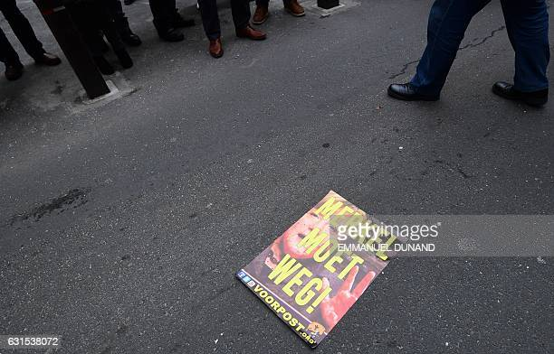 TOPSHOT A placard reading 'Merkel must go' lies on the ground during a protest of Belgian farright activists in front of the venue where German...
