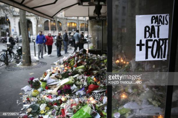 """Placard reading """"Paris beats stronger"""" is placed at the candles and flowers placed at the entrance of the cafe 'La Belle Equipe', Rue de Charonne, on..."""