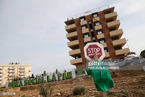 A placard reading 'Stop Evictions' stands in a plot next to the block of flats occupied by the anti evictions platform on October 15 2013 in Salt...