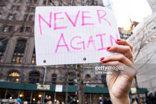 A placard reads 'Never Again' seen during the National School Walkout a 17 minute walkout by students in honor of the 17 people who died one month...