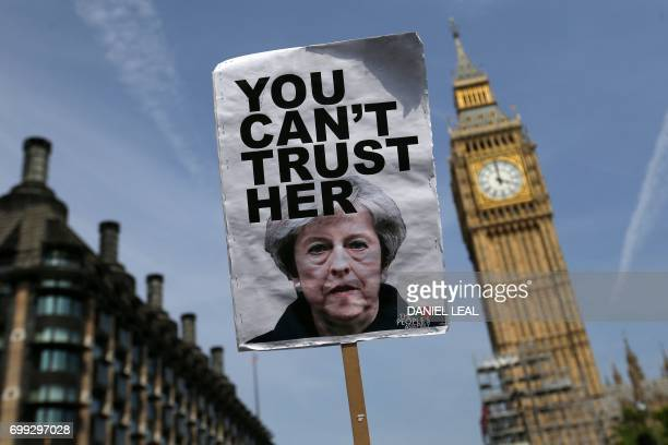 TOPSHOT A placard showing a picture of Britain's Prime Minister Theresa May saying 'You can't trust her' is raised in front of the Elizabeth Tower...