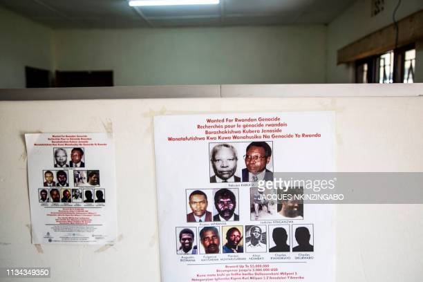 A placard showing the names and pictures of the wanted fugitives is stuck on a wall at the headquarters of the Genocide Fugitives Tracking Unit a...