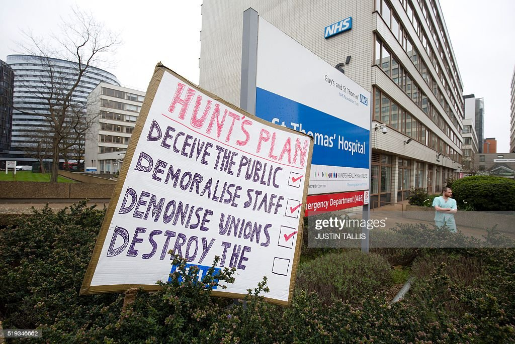 A placard sits in a hedge outside St Thomas' Hospital in central London on April 6, 2016, as junior doctors strike against proposed new conditions and pay rates for working unsociable hours. Thousands of operations and procedures across England have been cancelled as a result of the 48 hour strike which began Wednesday morning. / AFP / JUSTIN