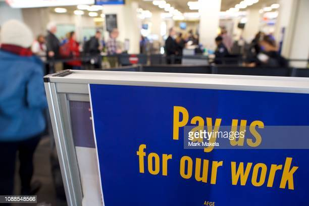 A placard stating Pay us for our work is displayed on a security line after Philadelphia Airport TSA and airport workers held a protest rally outside...