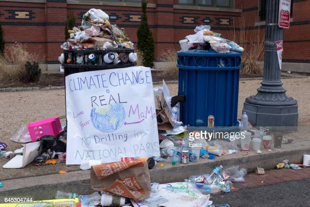 A placard warning against the dangers of climate change used in the March on Washington stands by an overflowing garbage can January 21st 2017 up to...