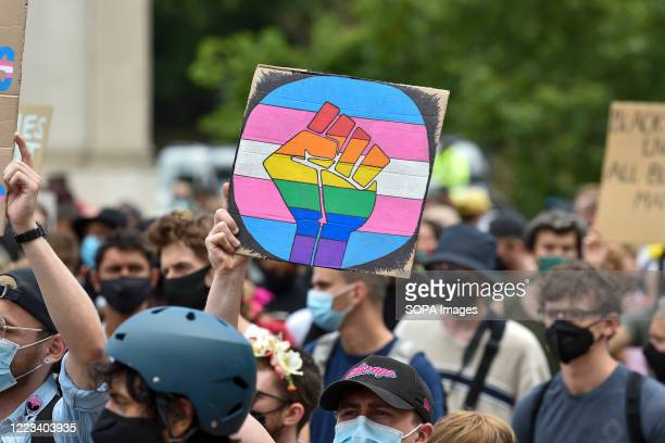 Placard with a fist in pride rainbow colours at the Black Trans Lives Matters' march in London. Thousands of activists have marched through London in...