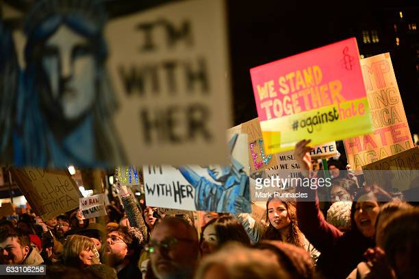 placards are held aloft as crowds listen to a speaker at the Mound as demonstrators march to the Scottish Parliament to protest against President...