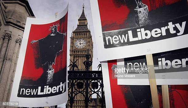 Placards bearing the head of the Statue of Liberty on the body of one of the Abu Ghraib prisoners are held aloft in front of the Houses of Parliament...