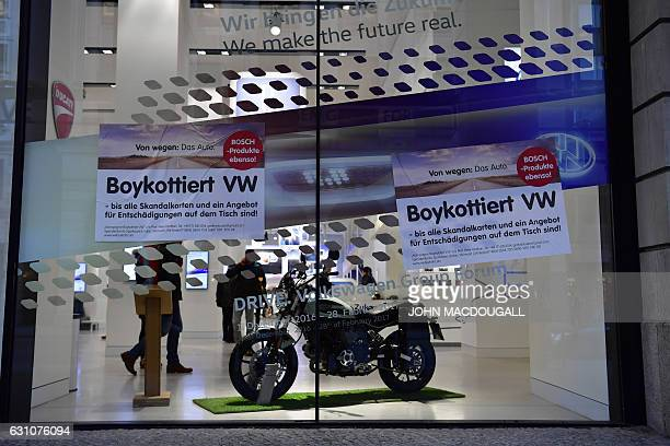 Placards calling for a boycott of Volkswagen cars are pasted on the windows of Volkswagen's main showroom in Berlin on January 6 2017 'Boycott...