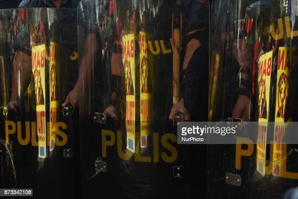 Placards containing the image of US President Donald Trump reflect on police shields as protesters from southern Philippines try to get past antiriot...