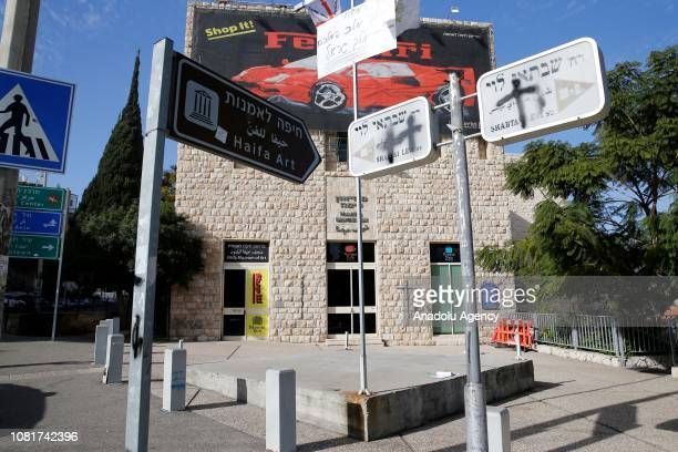 Placards flags are hung and spray painted are made on direction signs by Christians protesting the exhibition in front of the Haifa Museum of Art in...