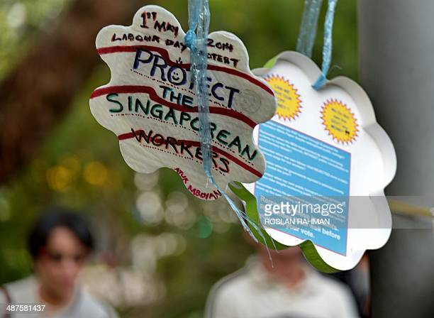Placards hang on nylon rope at speakers corner during a labour day