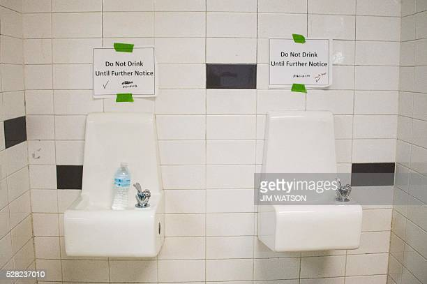 Placards posted above water fountains warn against drinking the water at Flint Northwestern High School in Flint Michigan May 4 where US President...