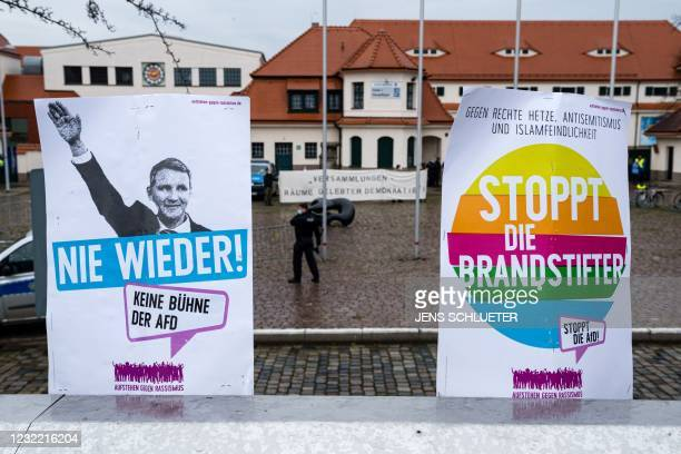 Placards reading 'Stop the arsonists' and showing Thuringia's leader of Alternative for Germany party Bjoern Hoecke with the lettering 'Never again'...