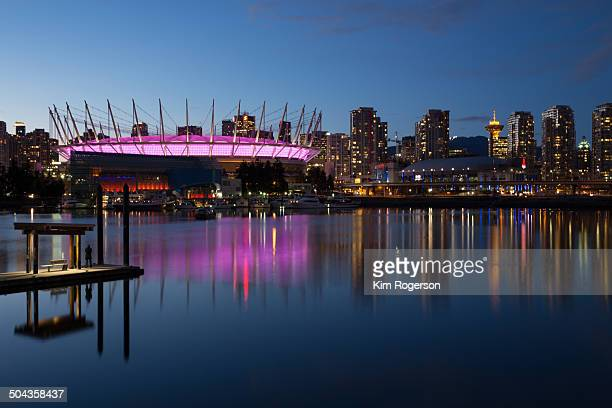 Place in English Bay is lit up in pink during blue hour, while a man waits for the ferry.