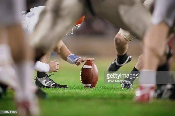 place kick holder positions football for kicker. - donner un coup de pied photos et images de collection