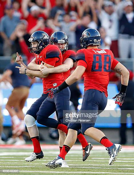Place kicker Casey Skowron of the Arizona Wildcats celebrates with Drew Riggleman and Trevor Wood after Skowron kicked the game winning 47 yard field...