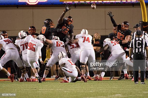 Place kicker Clayton Hatfield of the Texas Tech Red Raiders misses an extra point kick as Oklahoma State players apply pressure during the second...