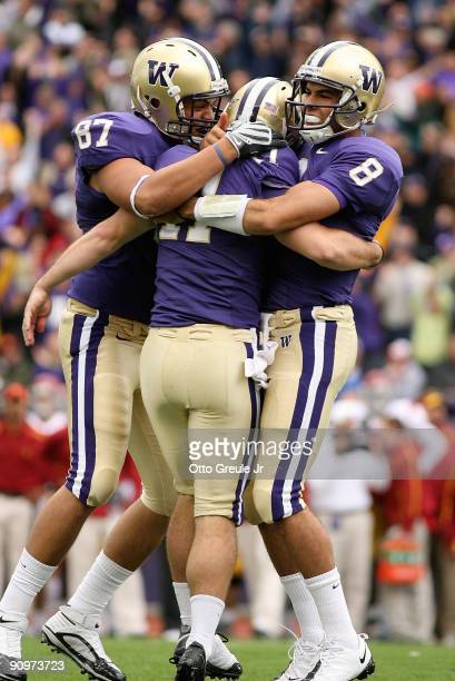 Place kicker Erik Folk of the Washington Huskies is congratulated by Romeo Savant and Ronnie Fouch after kicking the winning field goal to defeat the...