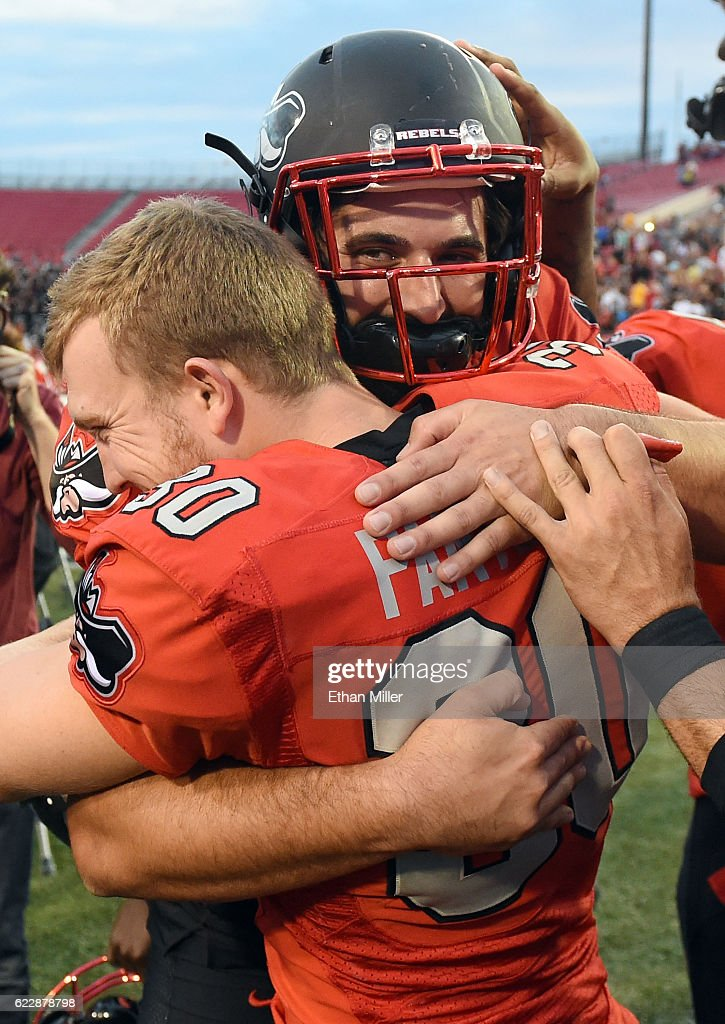 Place kicker Evan Pantels #30 hugs place kicker Nicolai Bornand #40 of the UNLV Rebels after Bornand hit a 41-yard field goal in triple overtime to defeat the Wyoming Cowboys 69-66 during their game at Sam Boyd Stadium on November 12, 2016 in Las Vegas, Nevada. Bornand replaced Pantels after he was injured during the game.